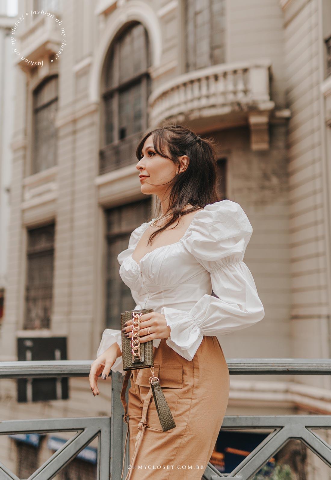 Foto look meio corpo blusa branca manga bufante e calça cargo marrom