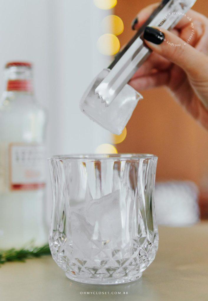 Mais do preparo do drinque, colocando o gelo no copo.