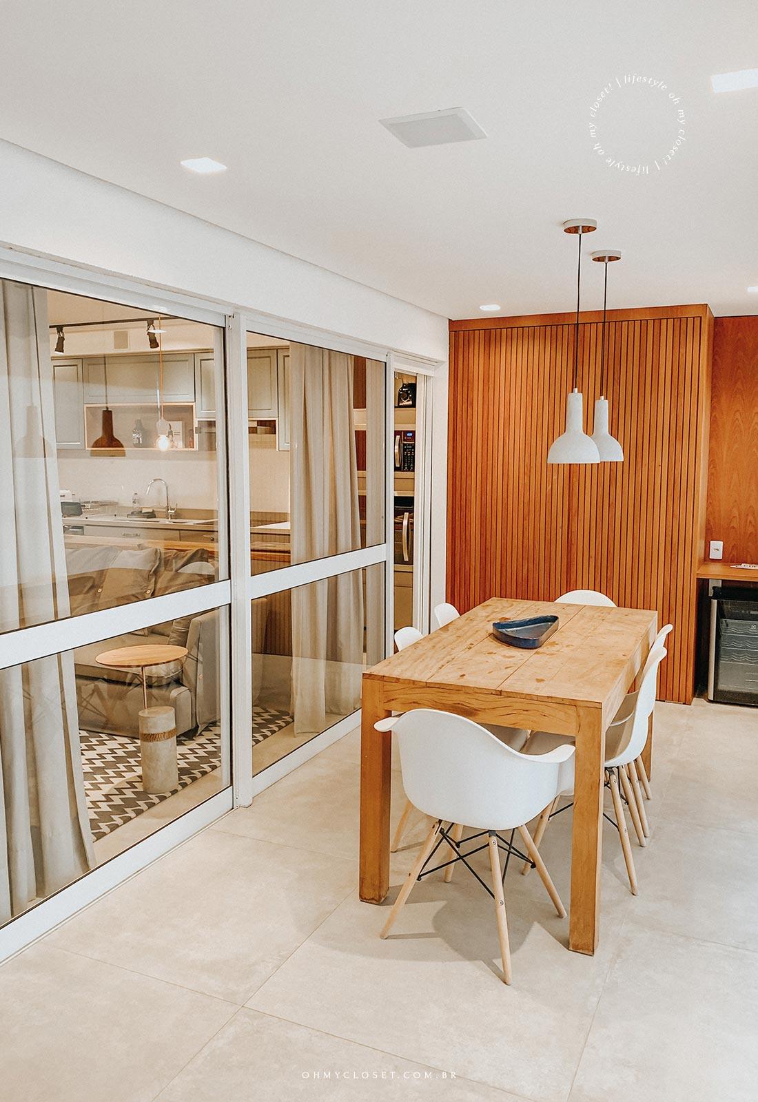 Vista mesa de jantar, adega e sala de TV com cozinha ao fundo, DNA Pinheiros.