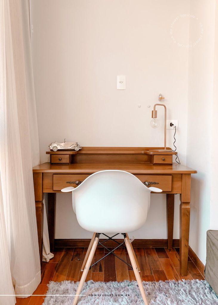 Área de trabalho com mesa rústica e cadeira Eifel branca na entrada da suíte master.