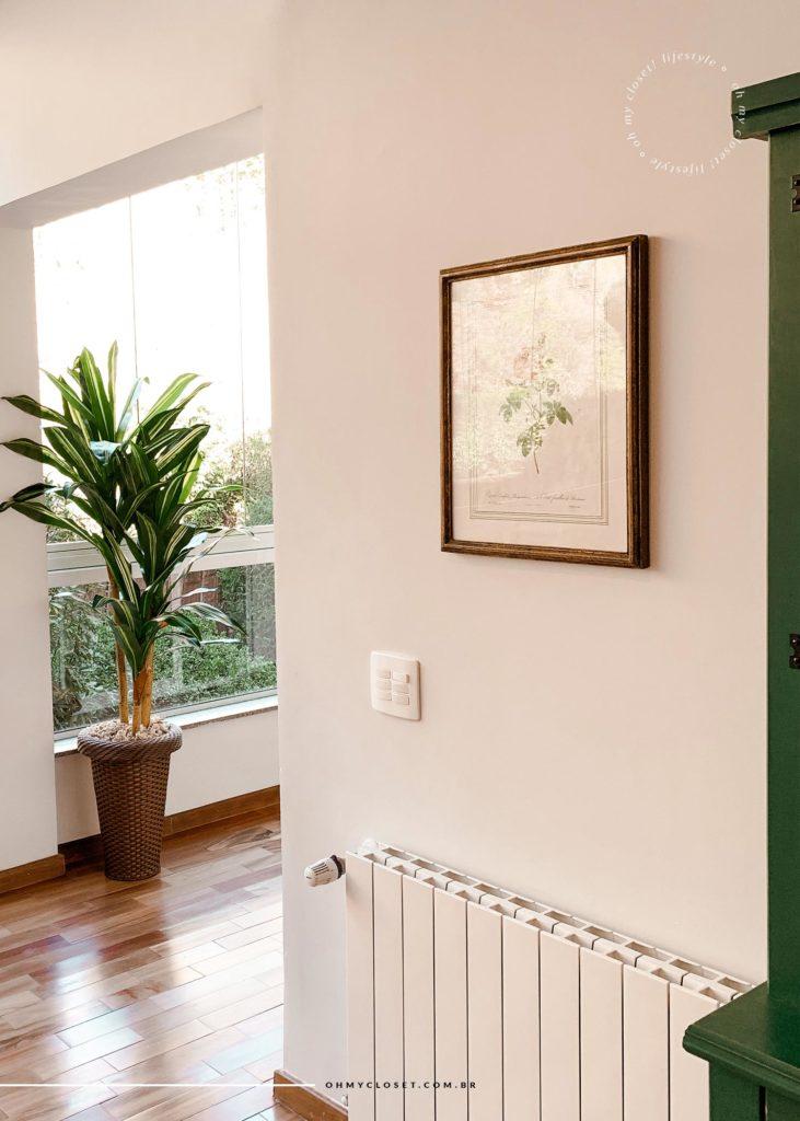 Decoração, quadro, e aquecedor próximo ao corredor dos quartos.