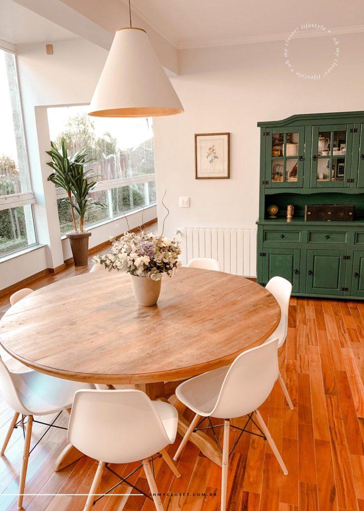 Close da mesa de jantar com a vista do corredor para os quartos no fundo.