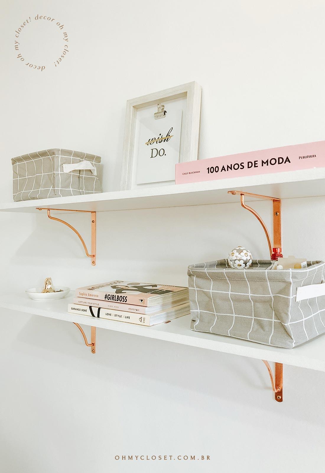 Prateleira branca com livros e decoração.