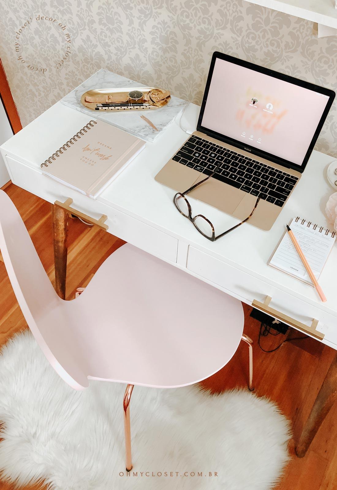 Home office com cadeira rosa, ferragens rose, mesa branca de madeira com pé palito.