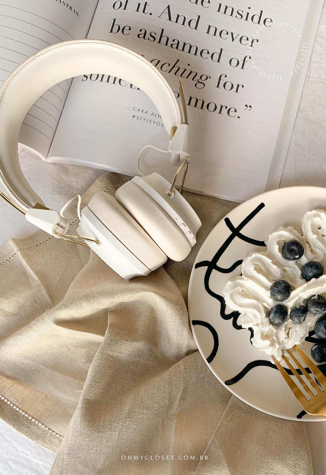 Flatlay, prato com blueberry e chantily, fone de ouvido e livro aberto.