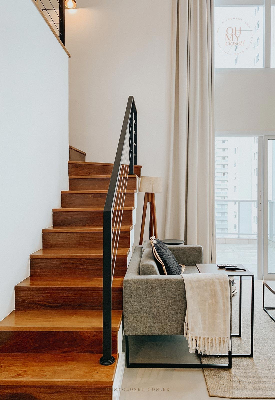 Escada e sofá da sala de tv Airbnb em São Paulo.