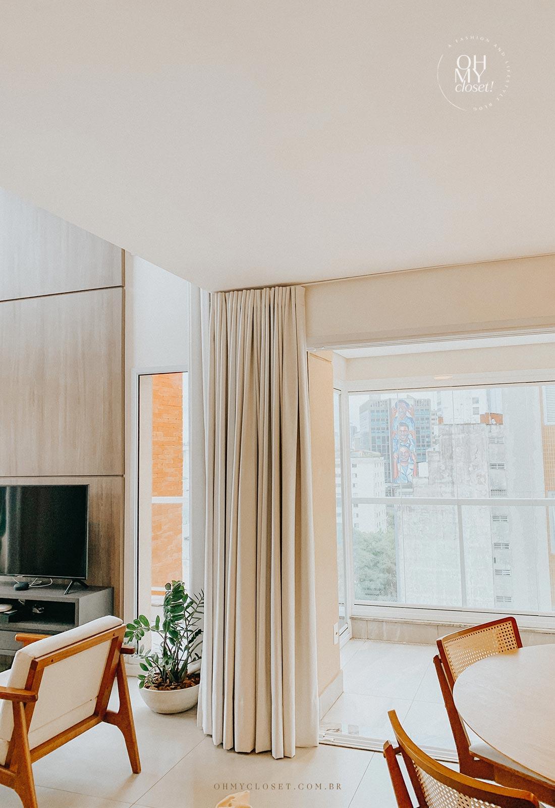 Sala de tv e sacada apartamento Airbnb nos Jardins em São Paulo.