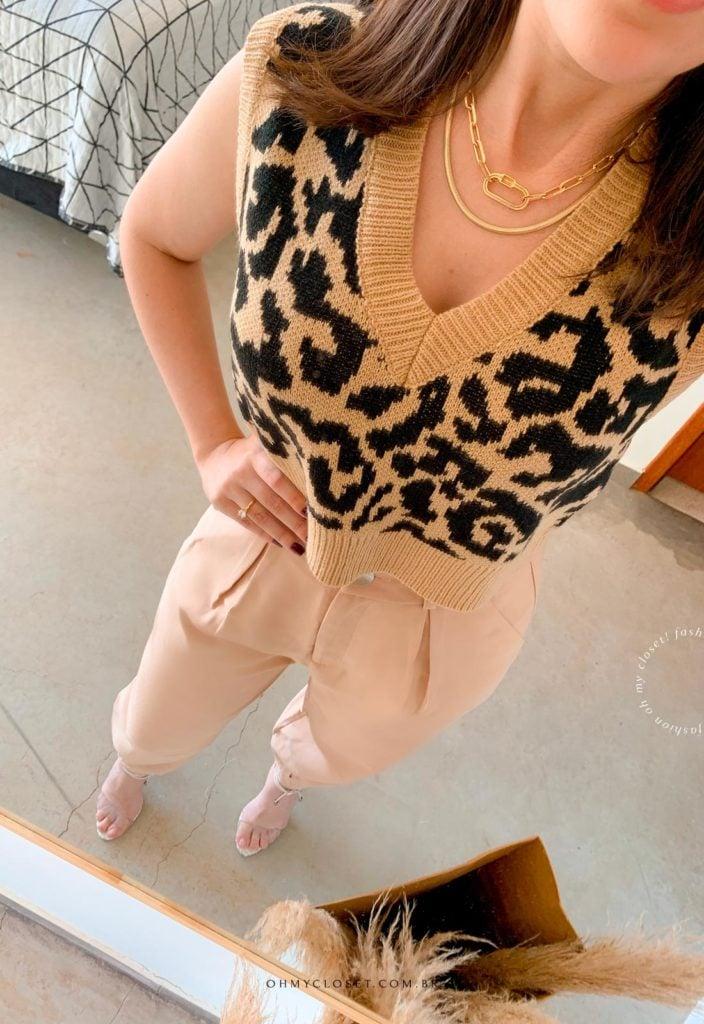 Look do dia com calça cenoura bege e colete de tricot cropped estampa de onça.