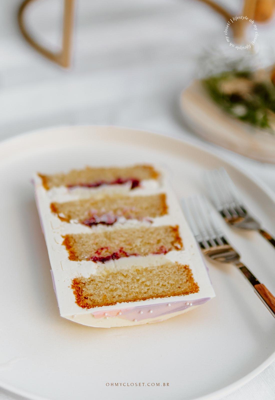 Fatia de bolo cortada, massa de baunilha, ganache de limão siciliano e geléia de frutas vermelhas.
