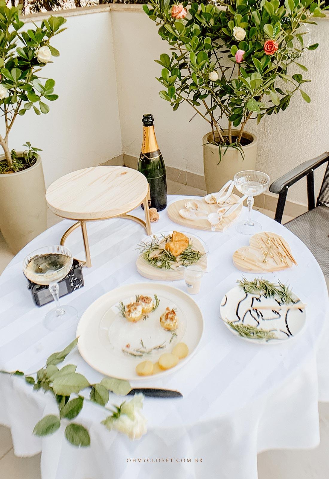Mesa de comida, sem o bolo, com decoração de rosas ao fundo.