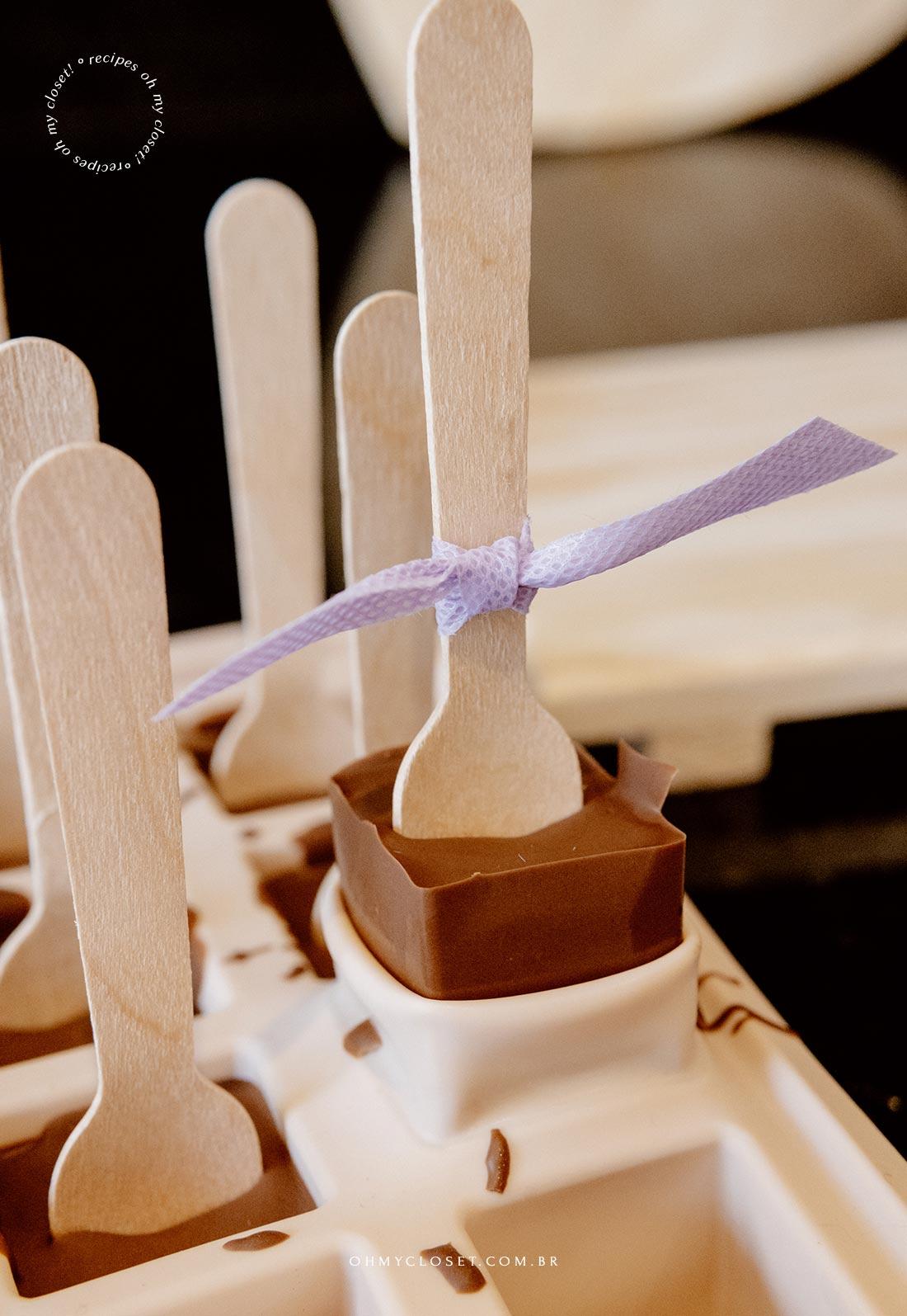 Tirando o chocolate no palito da forma de gelo. Chocolate quente no palito.