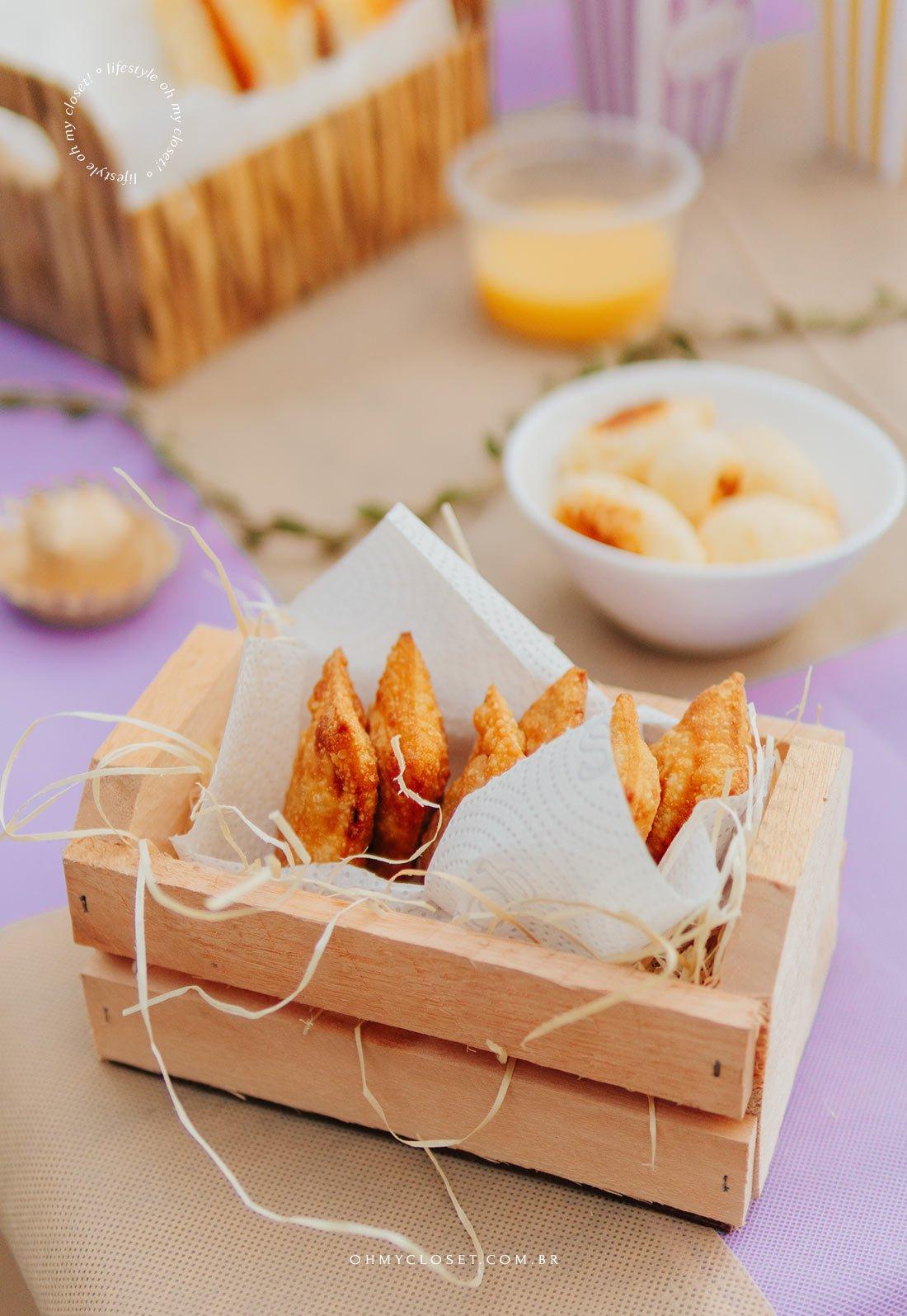 Detalhe dos pastéis na mesa de comida da festa junina em apartamento com pães de queijo ao fundo