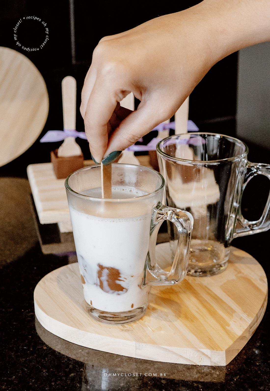 Mexendo o chocolate no palito no leite quente.