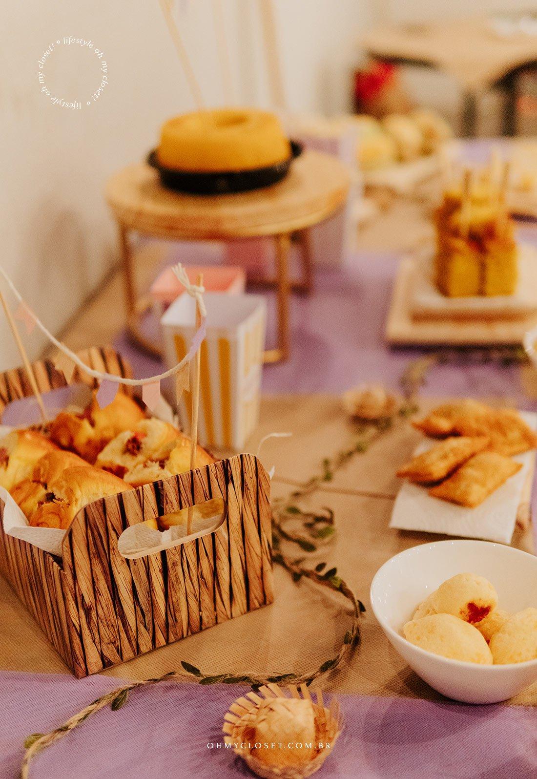 Mesa de comida da festa junina em apartamento com bolo, pastel, e pão de queijo