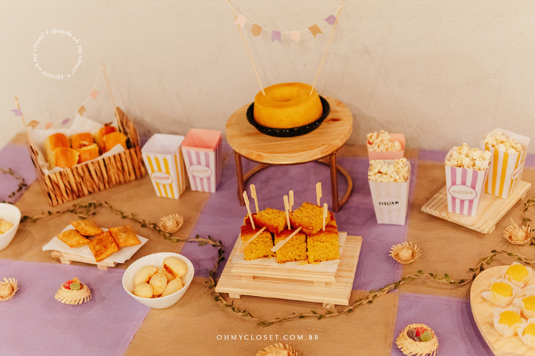 Festa junina em apartamento. Mesa de comida com cachorro quente pastéis pães de queijo bolo de milho pipoca quindim e doces.