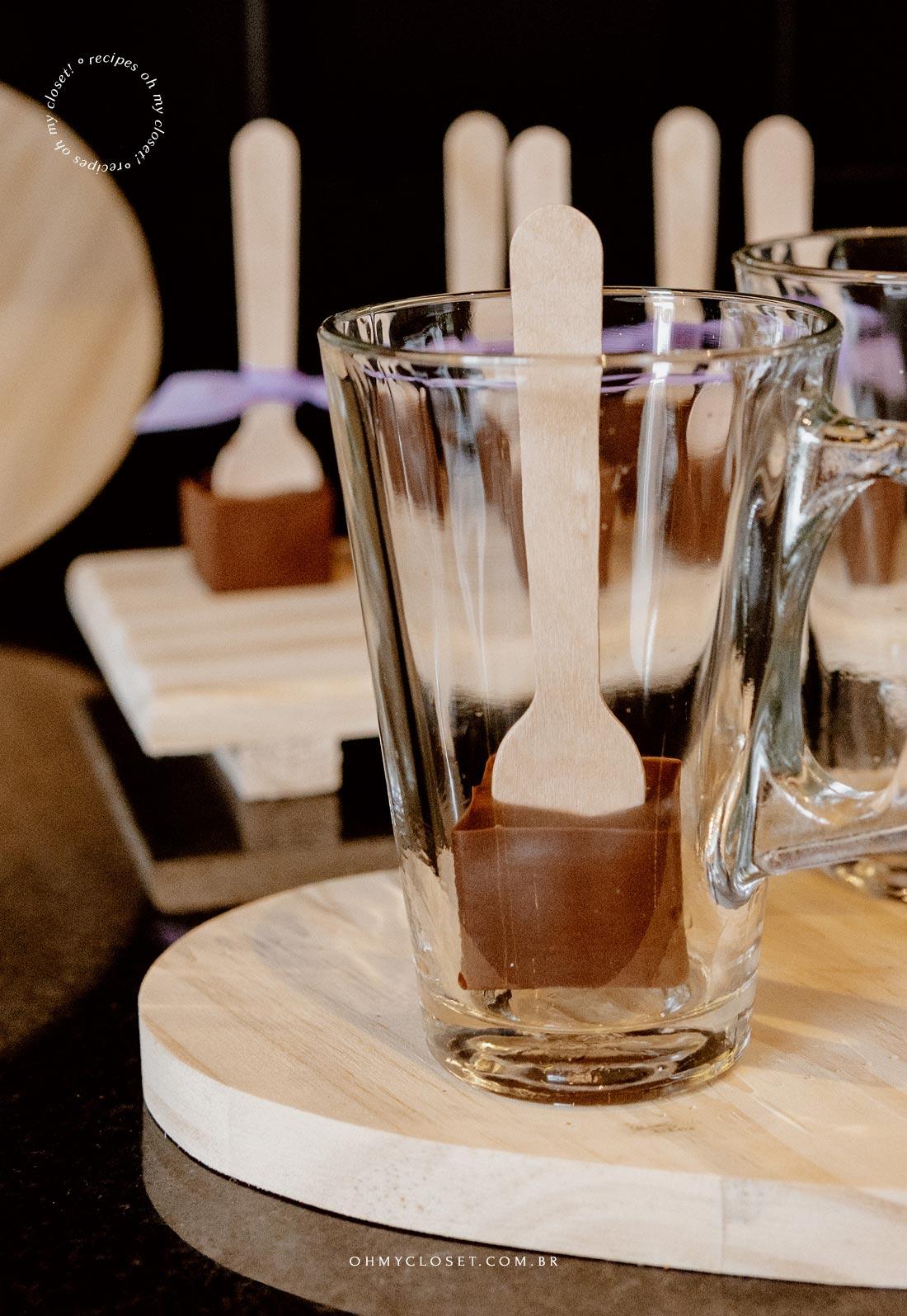 Chocolate no palito, dentro de uma xícara.